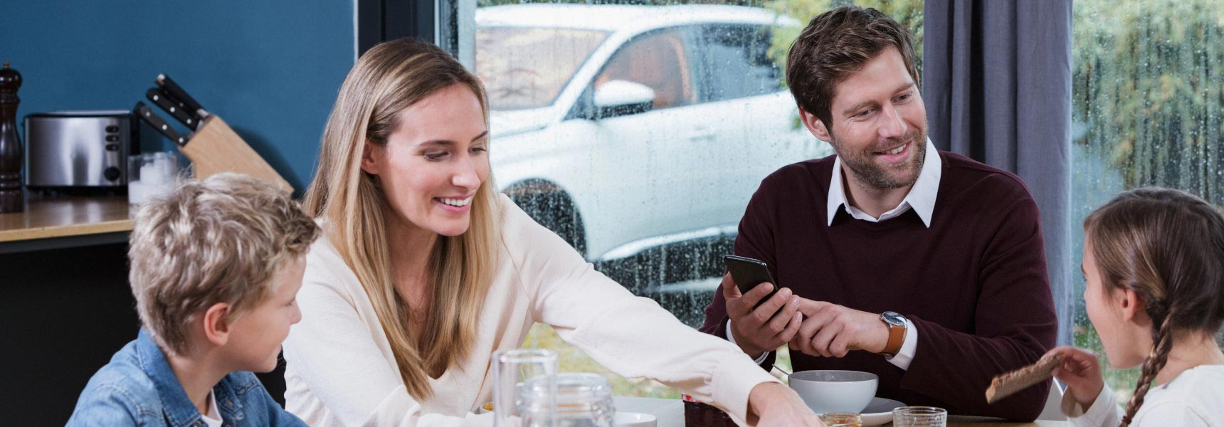 Family sitting cozily at the breakfast table while their car is pre-heated thanks to their Webasto parking heater.