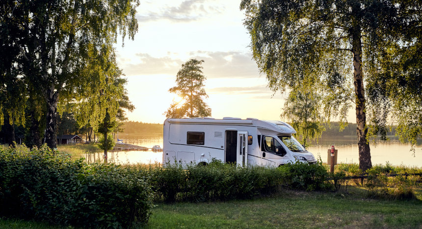 motor home in front of lake with sunset